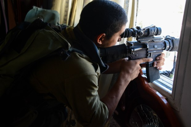 An Israeli paratrooper takes aim inside a Gazan building. From the IDF flickr page.