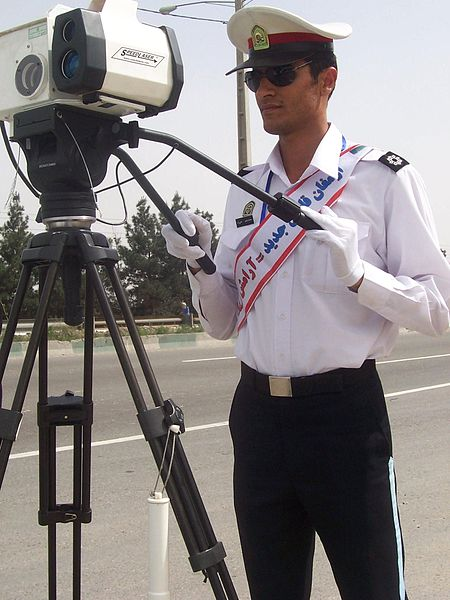 An Iranian policeman operates a speed gun. Via wikimedia.