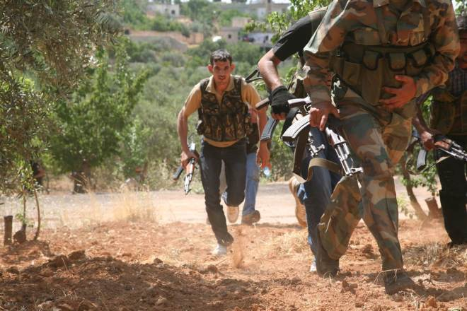 Syrian rebels from the Al-Qasas Brigade look for cover in an olive grove. By flickr user Syria Freedom.