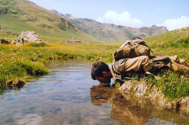 A Kurdistan Workers' Party solider drinks from a stream in Iraqi Kurdistan. By James Gordon.