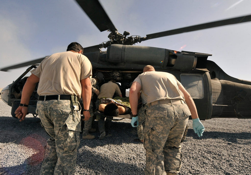U.S. army medics carry a wounded soldier onto a waiting Black Hawk helicopter at Combat Outpost Rath in Afghanistan. By the U.S. Department of Defense.
