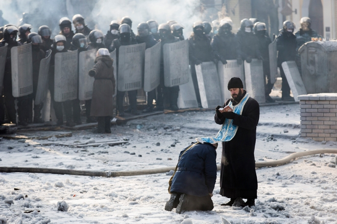 A man kneels before an Orthodox priest during the Euromaiden protests in Ukraine. By Jim Forest.