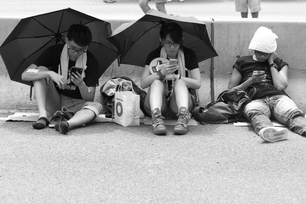 Protesters in Hong Kong play with their smartphones. By Kun-chia Wu.