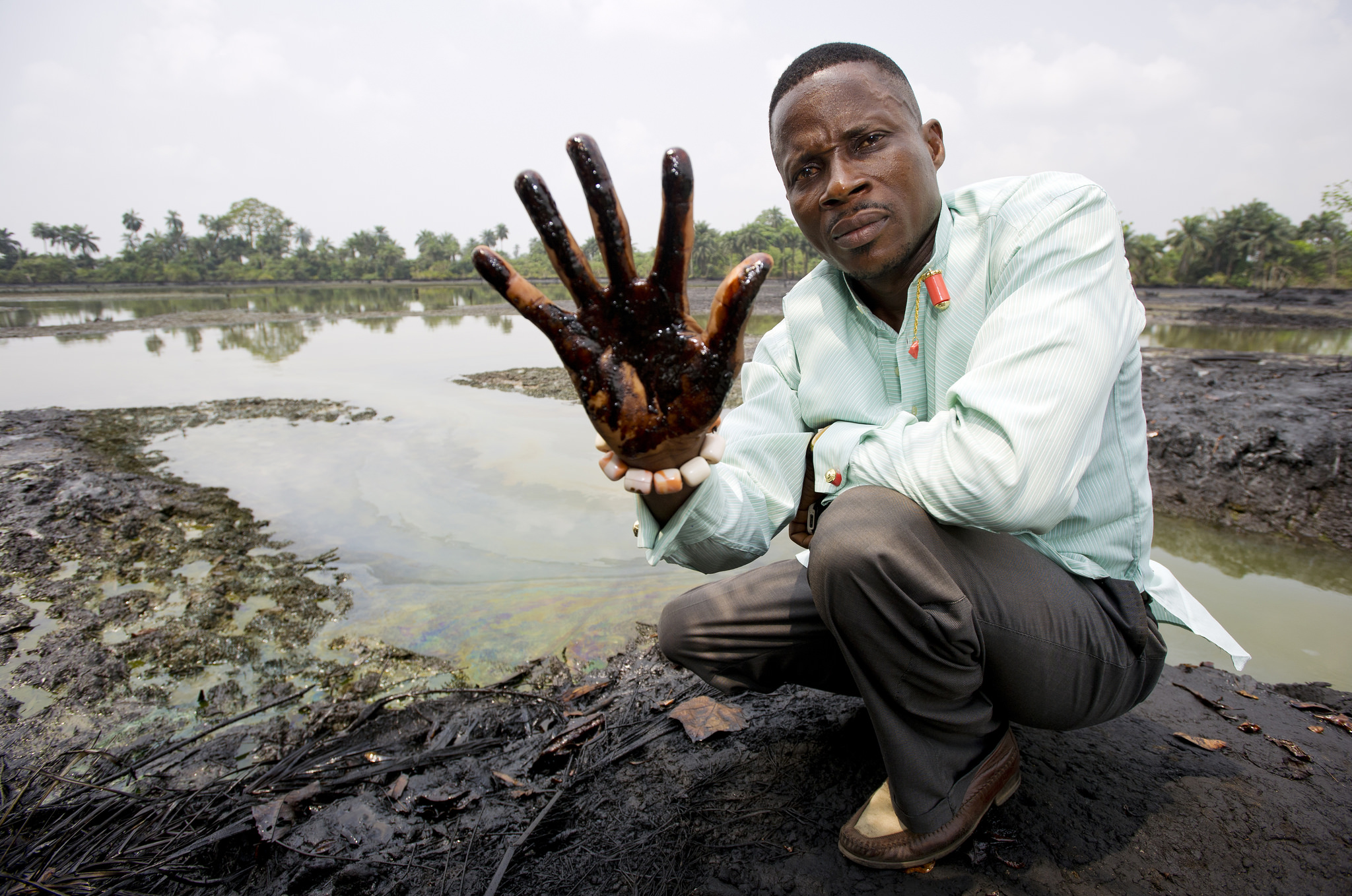 Plaintiff Eric Dooh shows the crude oil, allegedly from Shell pipeline leaks, that has affected the banks of the creek through his village of Goi. By Milieudefensie.
