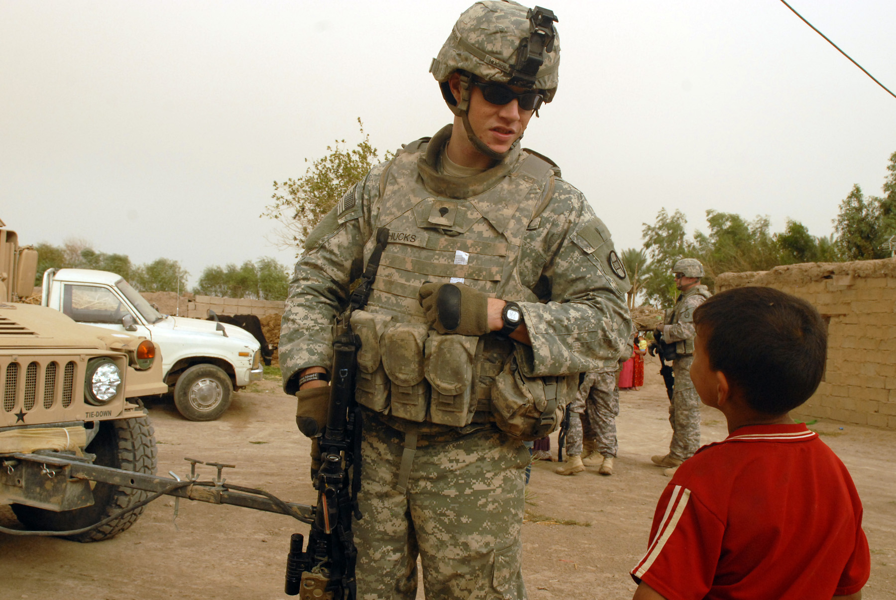 An American soldier talks to a child in Iraq. By the North Carolina National Guard.