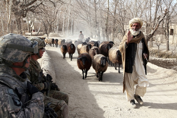 U.S. Army soldiers with Charlie Company, 2nd Battalion, 30th Infantry Regiment, 4th Brigade, 10th Mountain Division look on as an Afghan local waves to them in the Baraki Barak District, Logar province, Afghanistan, Dec. 20, 2010. By: Pfc. Donald Watkins.