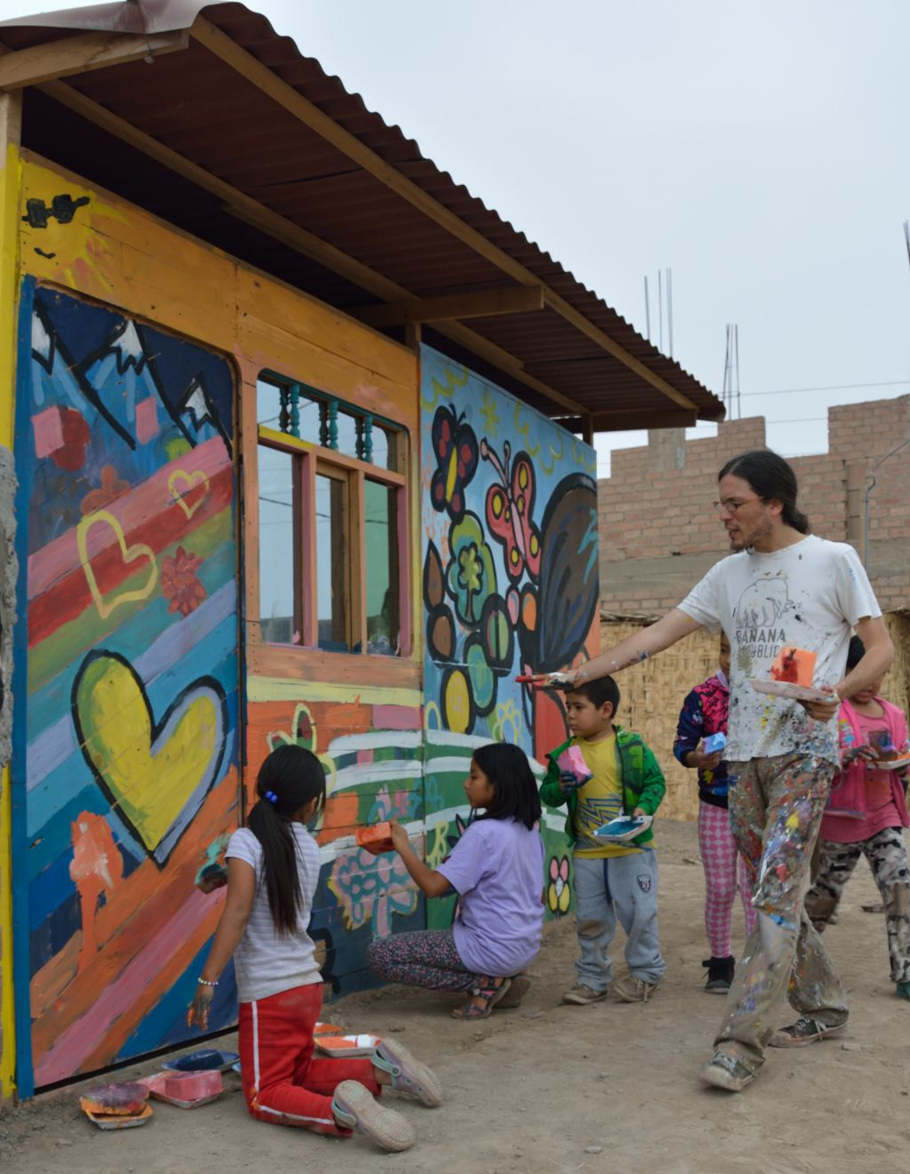 Mauricio Delgado and the Muralist Brigade work with children on a mural about literacy in San Lorenzo. By Steven T. Zech.