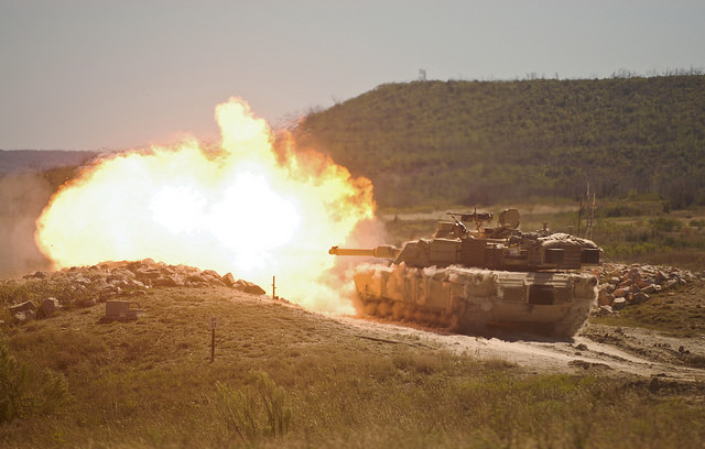 A burst of fire erupts from the muzzle of a 2nd Armored Brigade Combat Team, 1st Cavalry Division M1 Abrams tank during gunnery training at Fort Hood, Texas. By: U.S. Army Maj. Adam Weece)