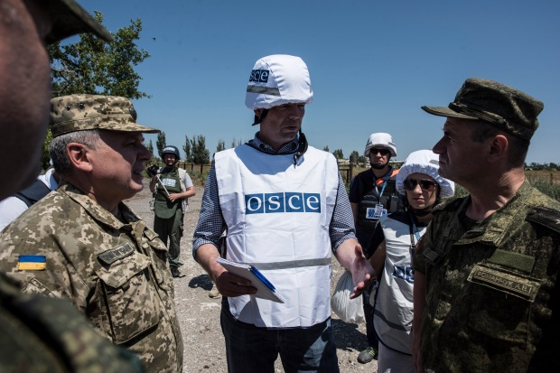 Deputy Chief Monitor of the OSCE Special Monitoring Mission to Ukraine, Alexander Hug (c), and two generals from the Joint Centre for Control and Co-ordination discussing situation in Shyrokyne, 4 July 2015. By OSCE/Evgeniy Maloletka.